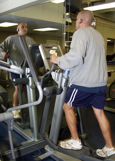 starší muž cvičící v posilovně na stepperu.jpg