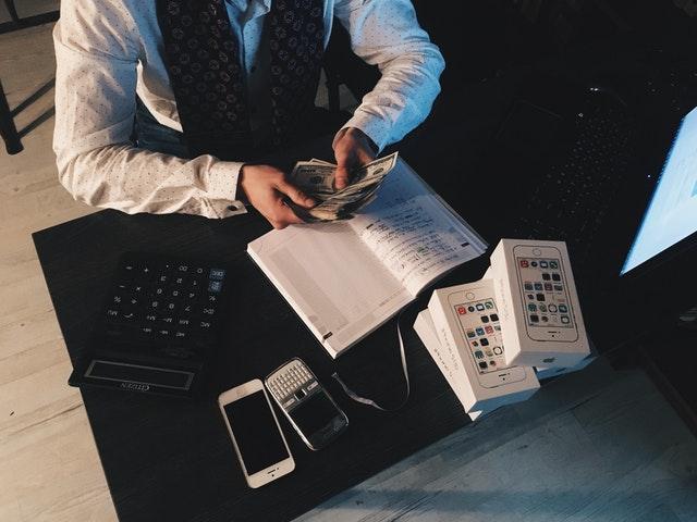 člověk počítá peníze za stolem
